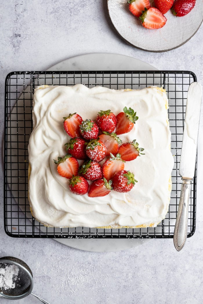 overhead photo of a frosted sponge cake with fresh strawberries on a baking rack