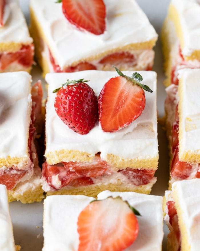 overhead photo of slices of sponge cakes with fresh strawberries