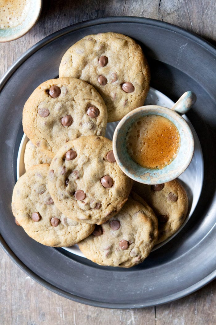 overhead photo of chocolate chip cookies on a platter with a cup of coffee