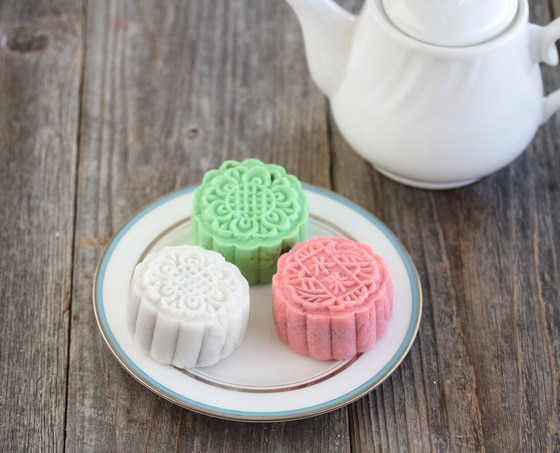 photo of a white, pink, and green mooncakes on a plate