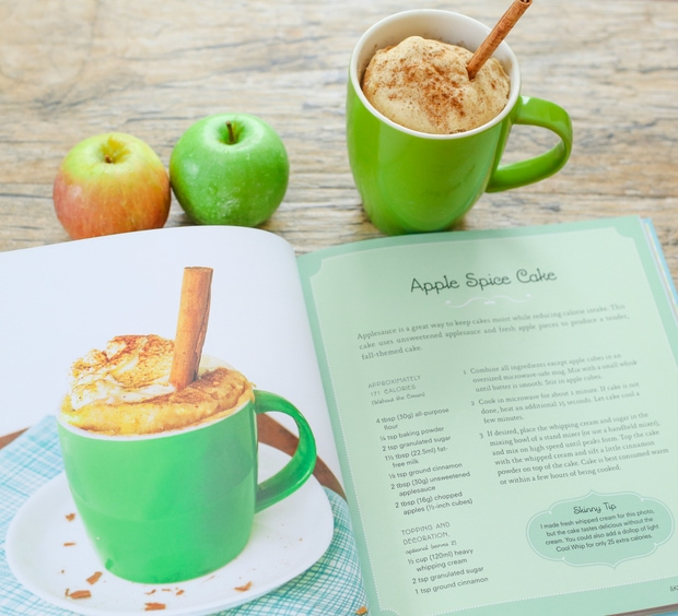 photo of an opened cookbook with a mug cake and two apples