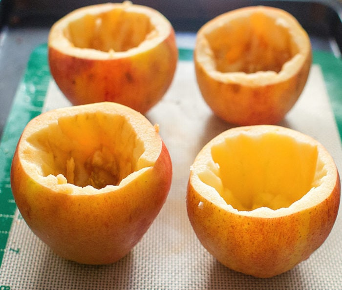 photo of four hollowed out apples