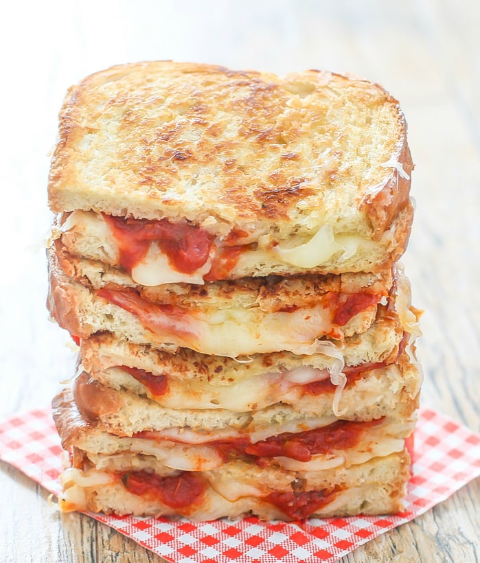 a stack of pizza grilled cheese sandwiches on a red and white checked napkin