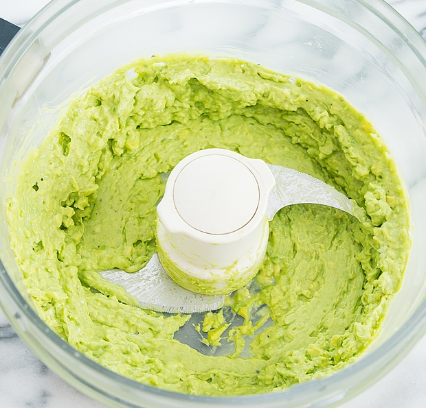 process photo showing what the avocado sauce looks like in the food processor