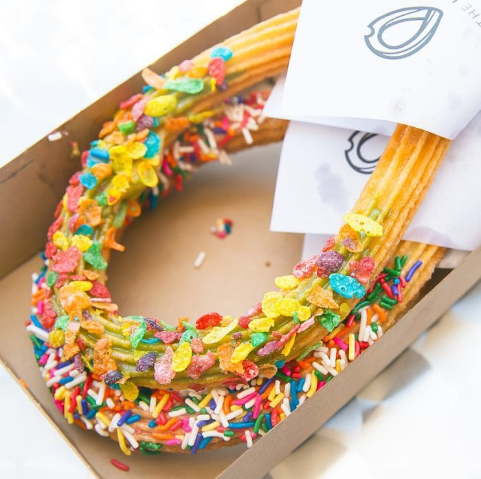 photo of one churro with sprinkles and one coated in fruit loopsc cereal