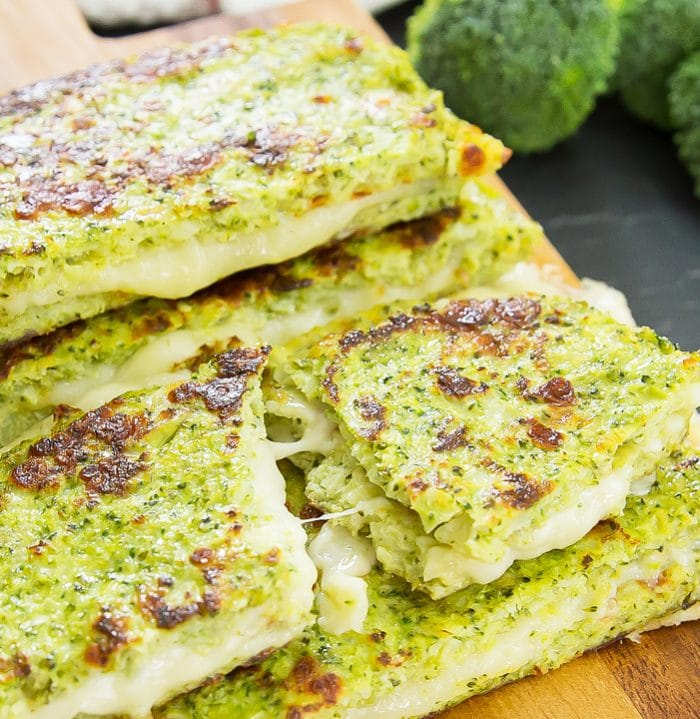 a close-up of a broccoli bread grilled cheese sandwich sliced in half with cheese oozing out