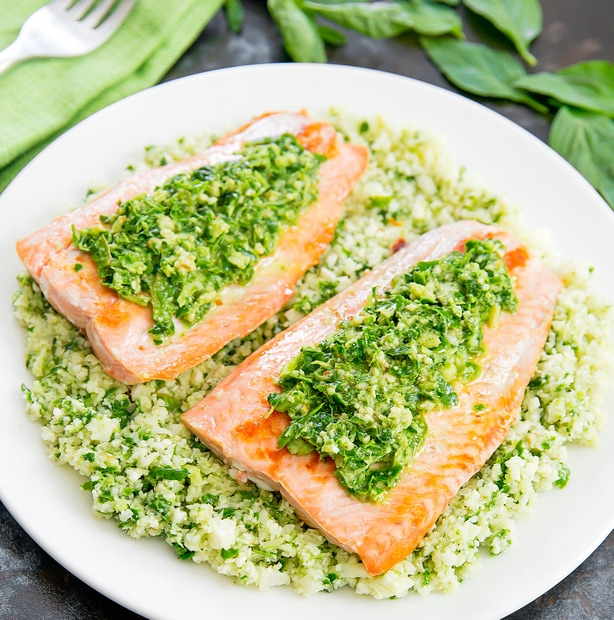 two salmon fillets on a bed of pesto cauliflower rice