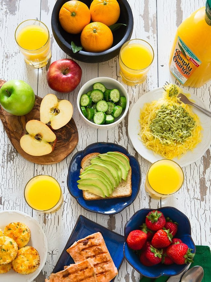 overhead photo of different lunch dishes with glasses of orange juice