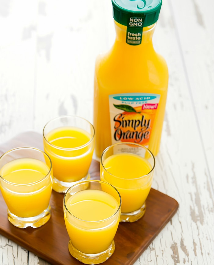 photo of four glasses of orange juice with Simply Orange bottle