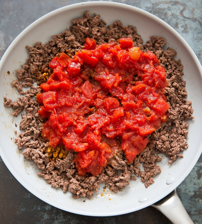 step by step photo of beef and tomatoes in a skillet