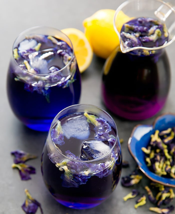 a top-down photo of 2 glasses of butterfly pea flower tea lemonade