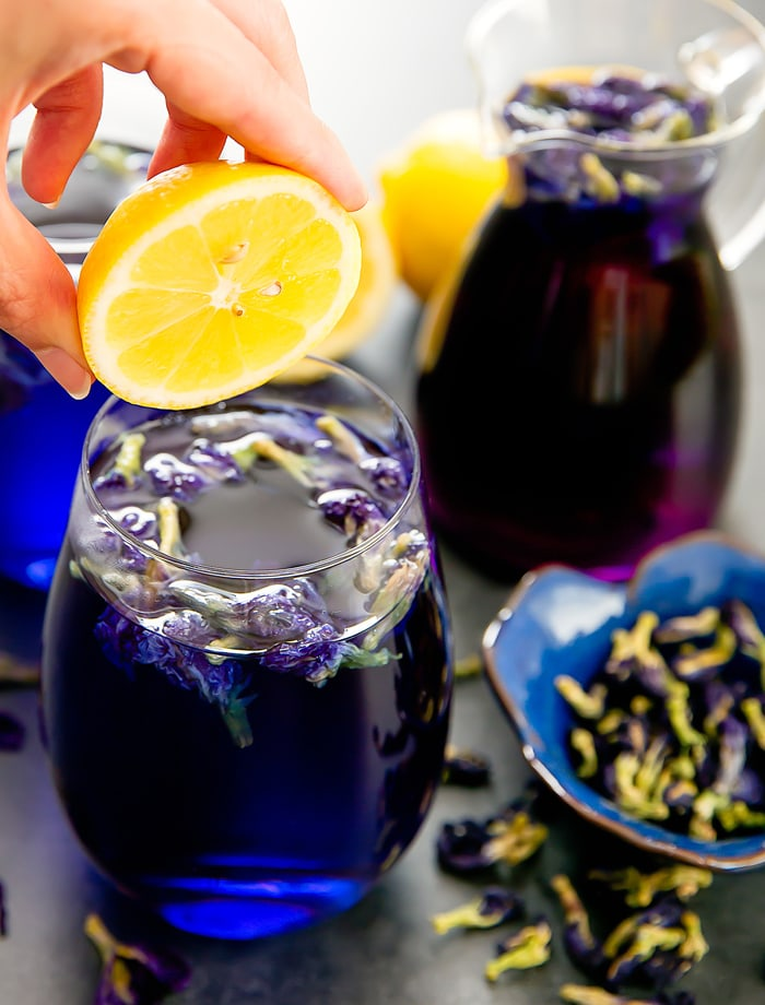 a close-up of a glass of Butterfly pea flower tea lemonade with someone about to squeeze lemon into it