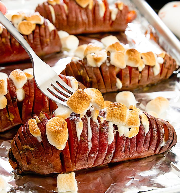 photo of a fork digging into a Marshmallow Stuffed Hasselback Sweet Potato