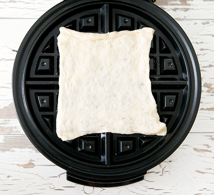 photo of one square of pizza dough in the waffle maker