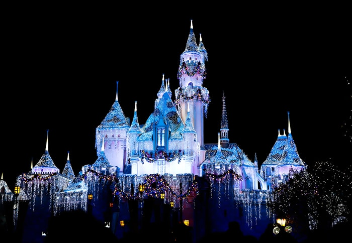 photo of the castle at disneyland lit up at night with lights