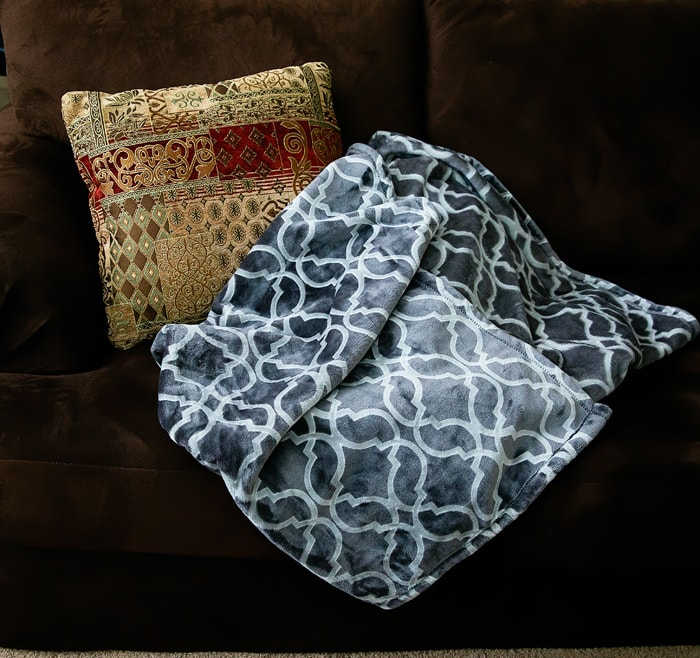photo of a pillow and blanket on a couch