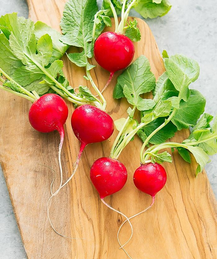 raw radishes on a cutting board