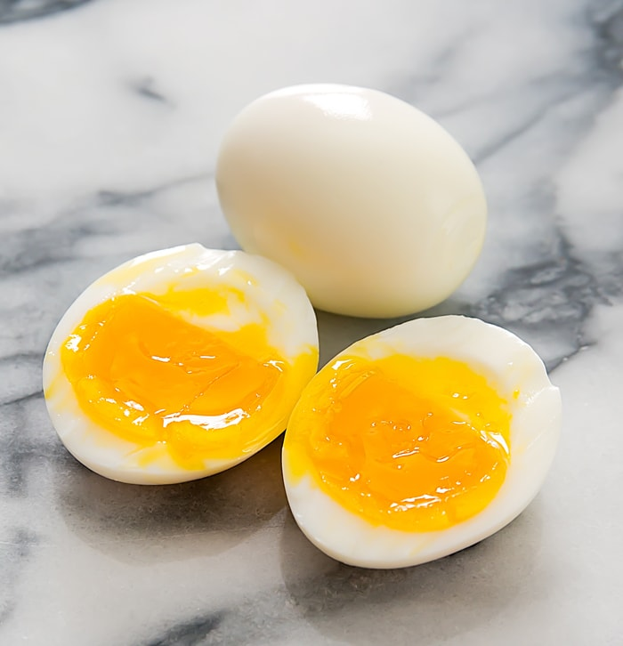 photo of a whole soft boiled egg and one that is slice in half