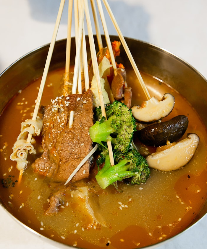 close-up of skewers in a bowl of broth