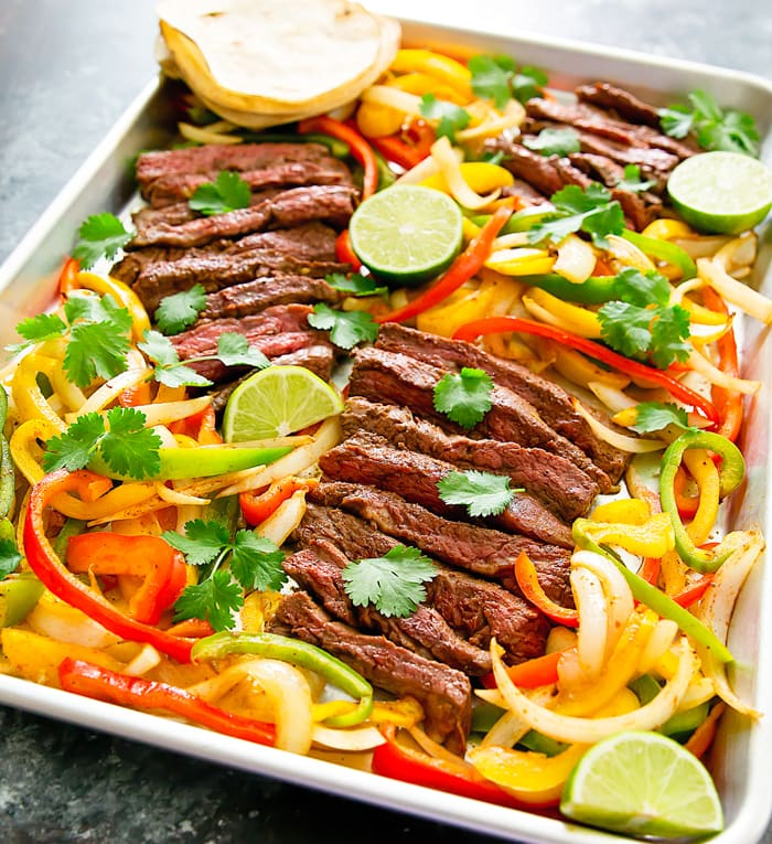 photo of steak and peppers on a sheet pan garnished with cilantro and limes