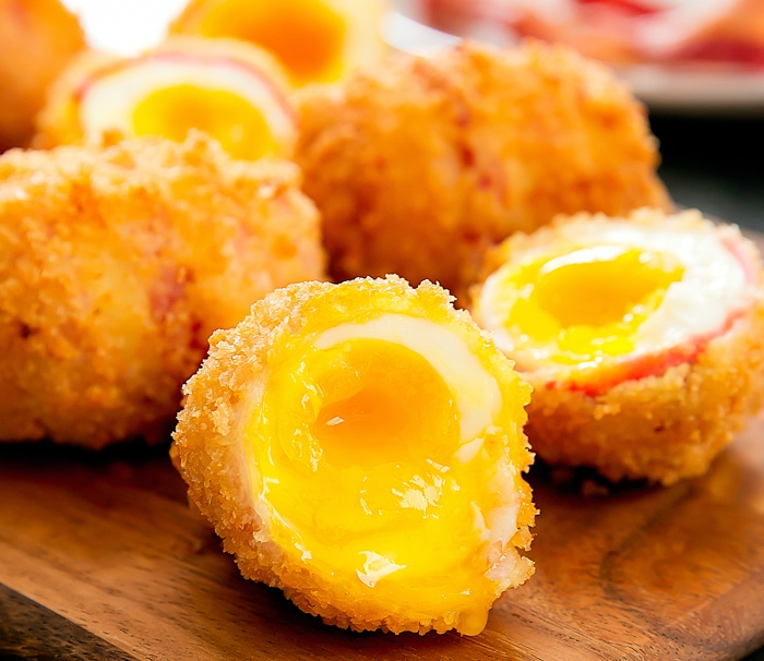 close-up of a fried bacon wrapped egg sliced in half to show the egg yolk