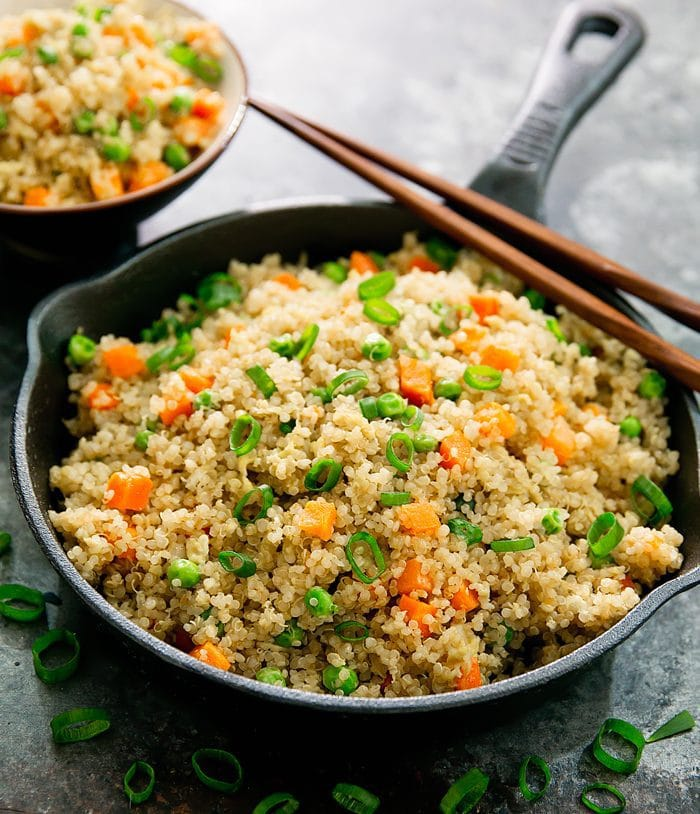 photo of Quinoa Fried Rice in a black skillet with chopsticks