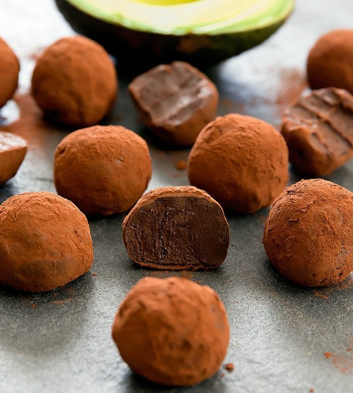 close-up photo of chocolate avocado truffles with one truffle sliced in half