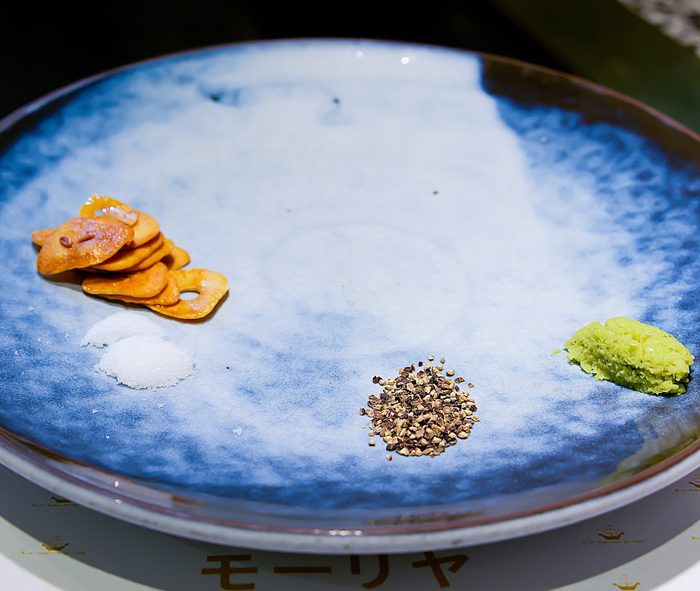 photo of garlic chips, pepper, and wasabi on a blue plate