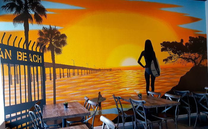 photo of a beach mural inside Pacific Poke Co