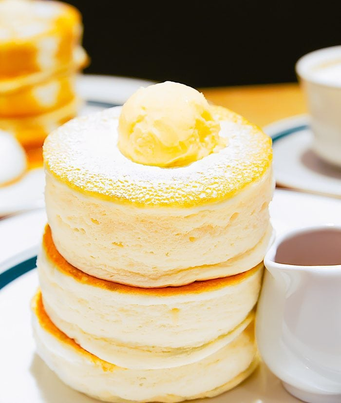 a stack of Japanese souffle pancakes topped with powdered sugar and butter