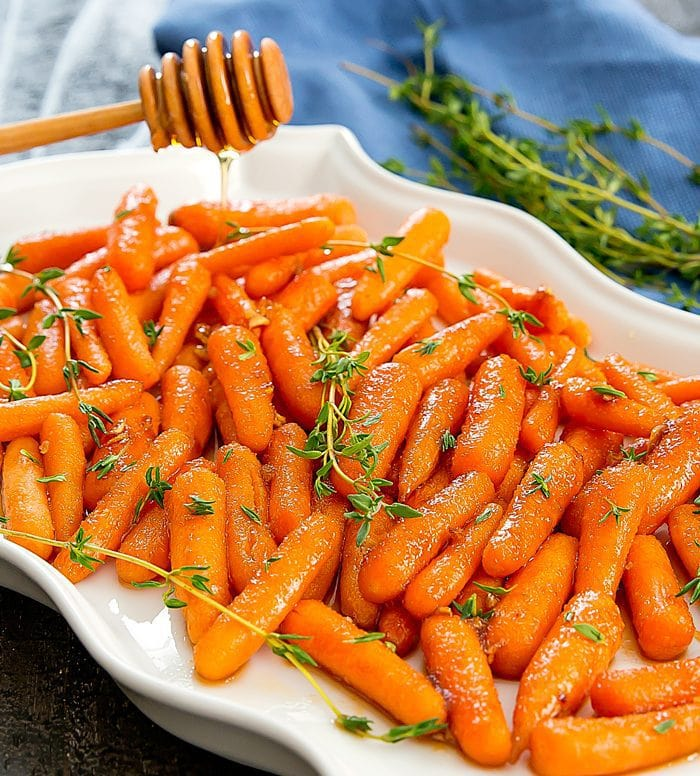 a plate of honey-garlic roasted carrots being drizzled with honey