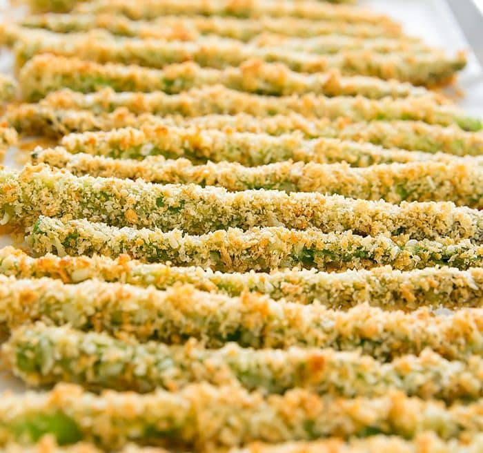 close up of asparagus fries lined up on a baking sheet