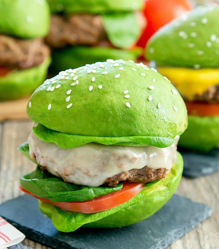 a close-up of a cheeseburger with avocado bun