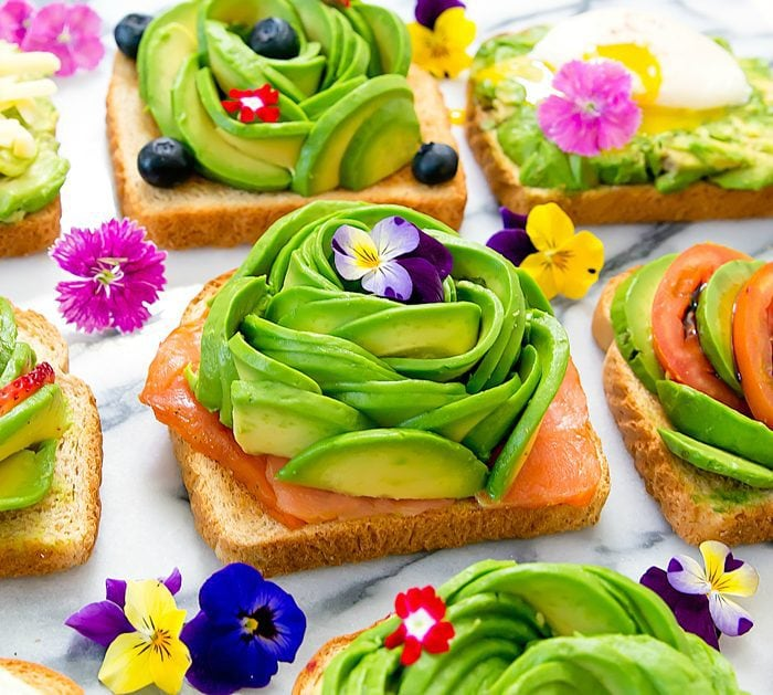 a close-up photo of toast topped with smoked salmon, an avocado rose, and fresh flowers