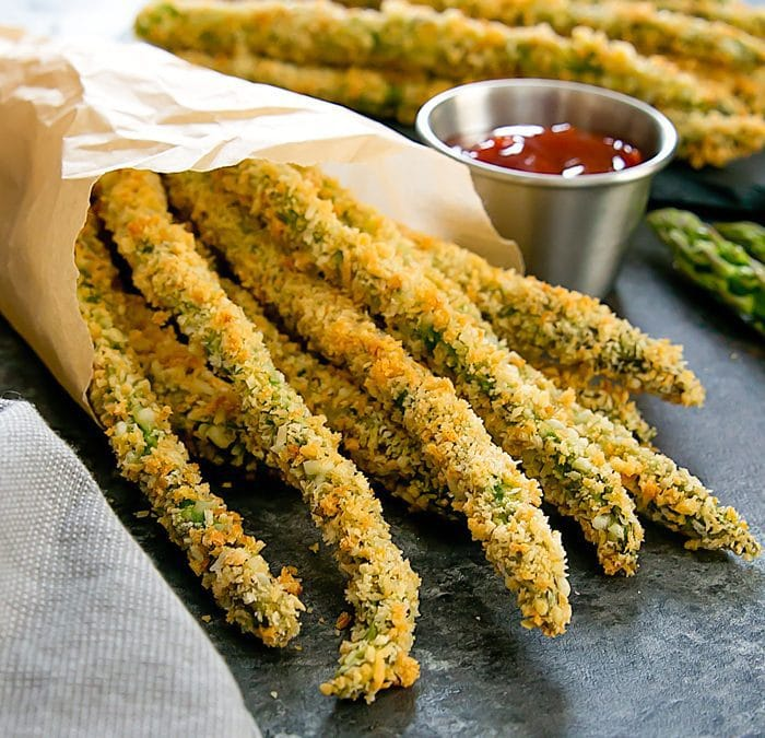 baked asparagus fries in a brown paper cone with dipping sauce on the side