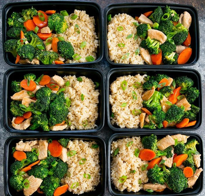 overhead photo of 6 meal prep containers with Chicken and Broccoli Stir Fry