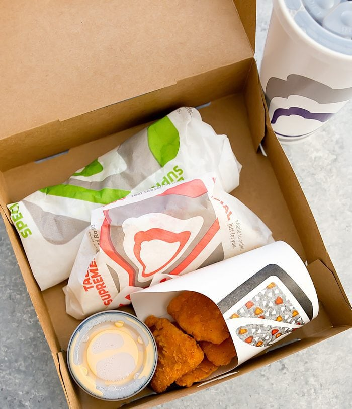 overhead photo Taco Bell Naked Chicken Chips Box with burrito, taco, Naked Chicken Chips, and cheese sauce