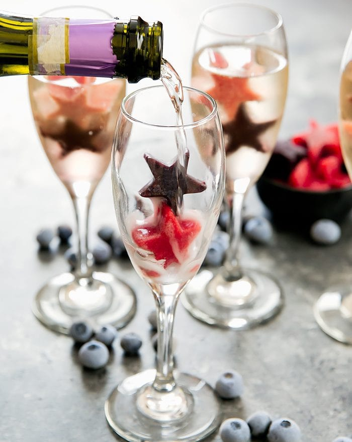 photo of champagne being poured into a glass with fruit ice