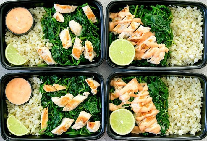 top-down photo of four meal prep containers with Skinny Bang Bang Chicken with Cauliflower Rice