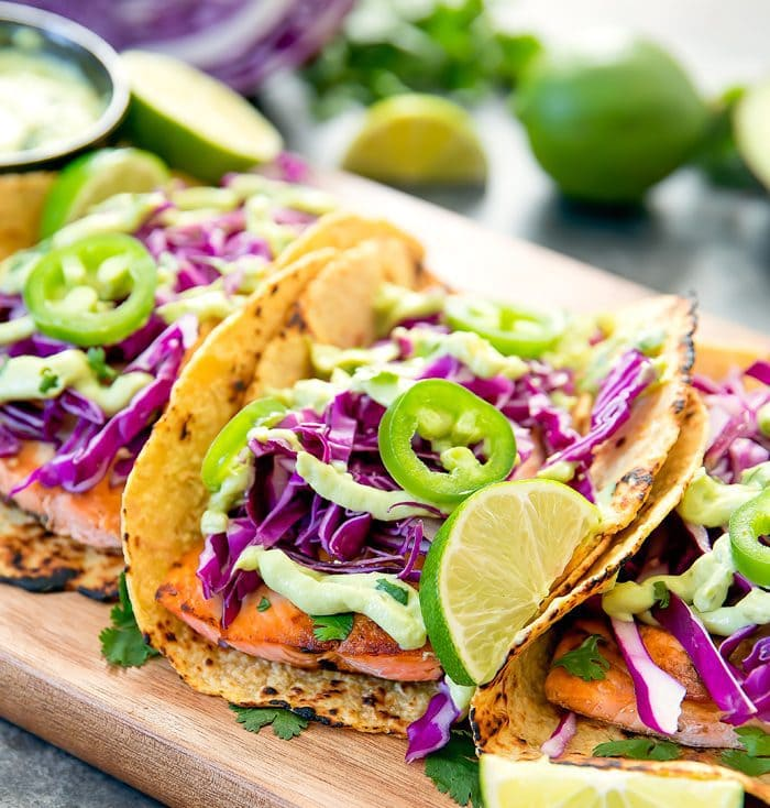 fish tacos garnished with avocado suace, red cabbage, and jalapenos