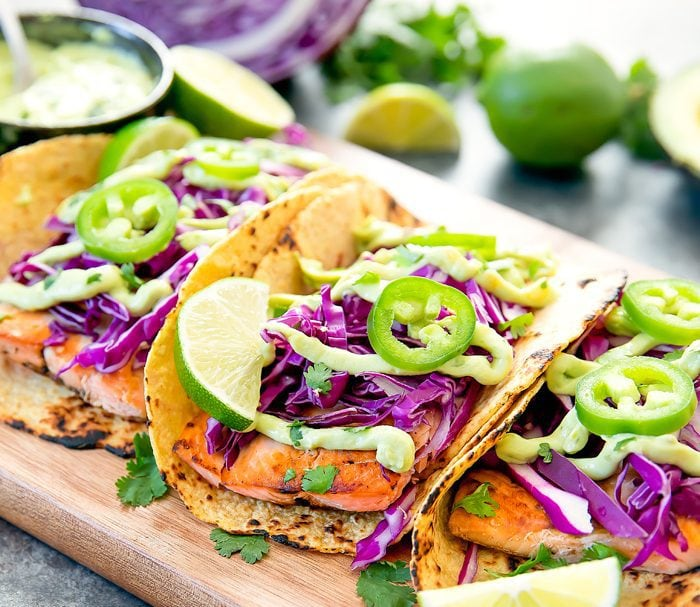 Fish tacos on a cutting board garnished with avocado sauce