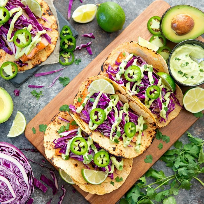 Three fish tacos with avocado sauce on a cutting board