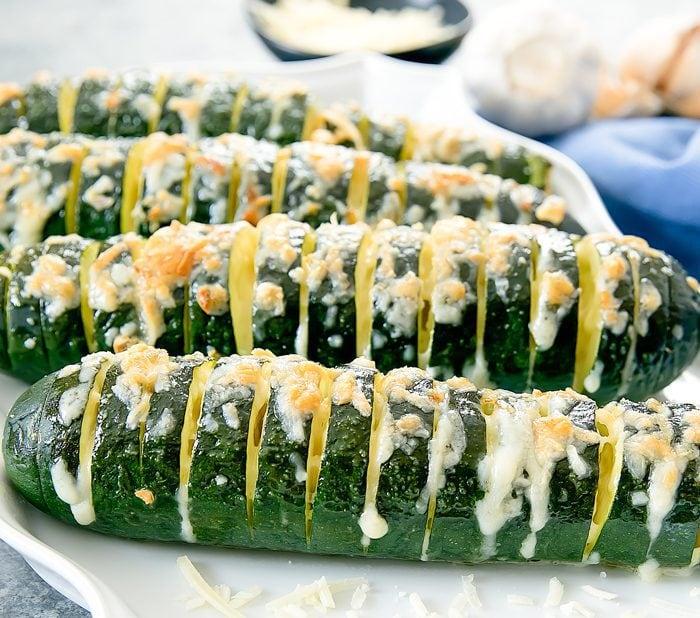 close-up of garlic parmesan hasselback zucchini on a white serving platter