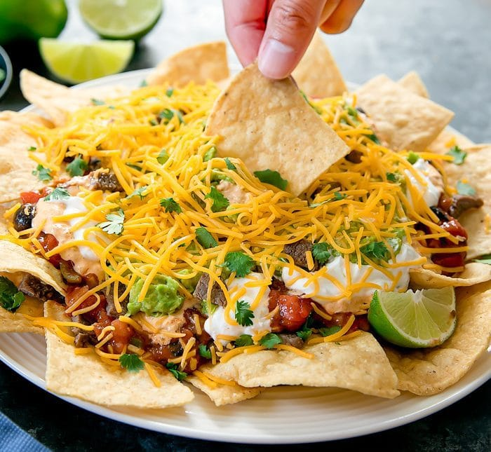 photo of a chip being dipped into the nachos