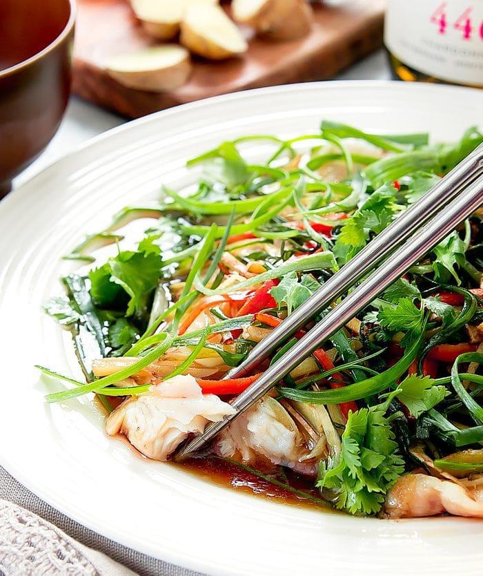 a close-up photo of chopsticks holding a piece of fish