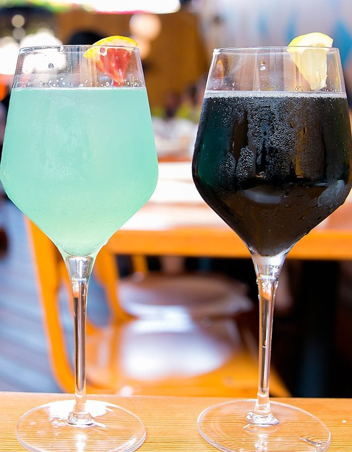 photo of a glass of blue magic mimosa and a black magic mimosa
