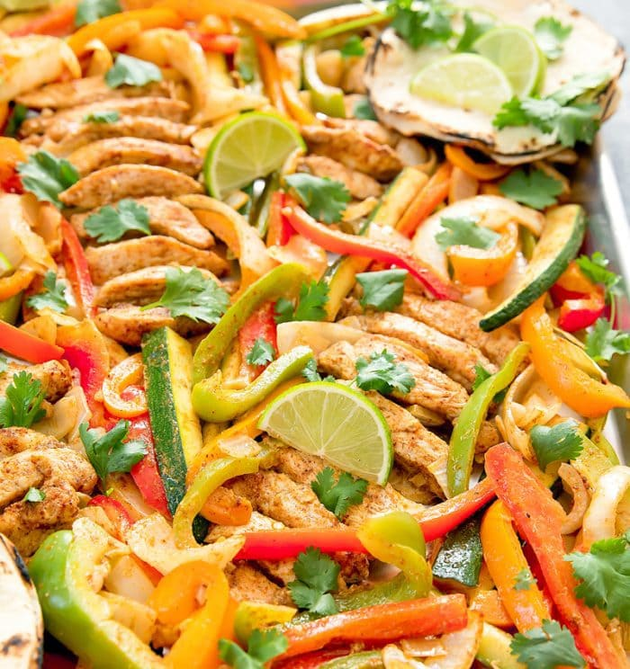 photo of Chicken Fajitas on a sheet pan garnished with lime wedges