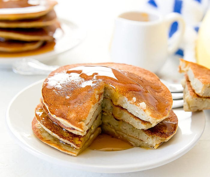 a stack of flourless banana pancakes topped with syrup and with a piece cut out