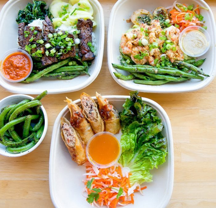 overhead photo of different dishes called Nom Nom Bento