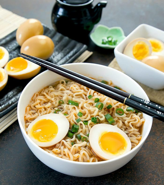 a bowl of ramen with a marinated soft boiled egg sliced in half